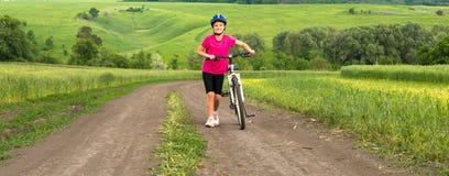 Muchacha deportiva con la bicicleta en campo verde Imágenes de archivo libres de regalías