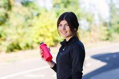 Muchacha deportiva con una botella para el agua en la calle al aire libre Fotografía de archivo libre de regalías