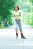 Muchacha deportiva del patinaje sobre ruedas en el parque rollerblading Imagen de archivo libre de regalías