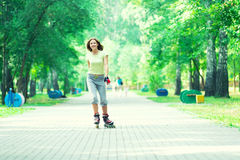Muchacha deportiva del patinaje sobre ruedas en el parque rollerblading Imagen de archivo