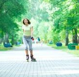 Muchacha deportiva del patinaje sobre ruedas en el parque rollerblading en patín en línea Imagen de archivo