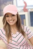 Muchacha deportiva en la sonrisa de la gorra de béisbol Fotos de archivo libres de regalías