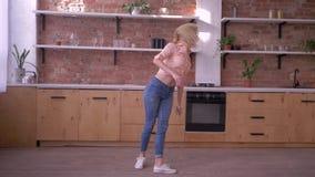 Muchacha deportiva feliz que hace tirón gimnástico en la cámara lenta en la cocina en casa metrajes