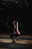 Muchacha deportiva fuerte que hace posiciones en cuclillas con el barbell Imagenes de archivo