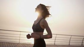 Muchacha deportiva joven que corre en una 'promenade' Mañana azul Camino de la playa Sensación libremente Forma de vida sana Carr almacen de video