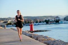 Muchacha deportiva joven que corre solamente en la puesta del sol hermosa cerca del lig foto de archivo