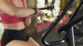 Muchacha deportiva motivada que comprueba la pulsera de la aptitud mientras que monta la bici inmóvil almacen de metraje de vídeo