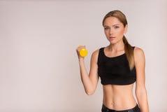 Muchacha deportiva que hace ejercicio con pesas de gimnasia y que mira la cámara Foto de archivo libre de regalías