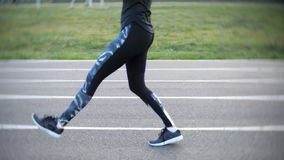 Muchacha deportiva que hace ejercicios de pierna en el estadio al aire libre almacen de metraje de vídeo