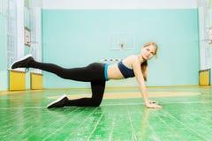 Muchacha deportiva que hace el oscilación de la pierna durante entrenamiento en gimnasio Fotografía de archivo