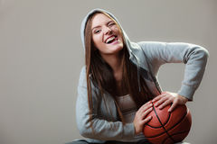 Muchacha deportiva que lleva a cabo baloncesto Imagenes de archivo