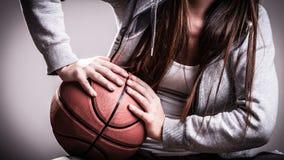 Muchacha deportiva que lleva a cabo baloncesto Fotografía de archivo