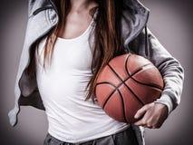 Muchacha deportiva que lleva a cabo baloncesto Imágenes de archivo libres de regalías