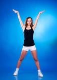 Muchacha deportiva que permanece con los brazos aumentados en fondo azul Imagenes de archivo