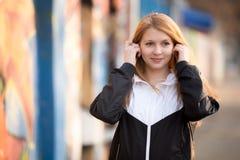 Muchacha deportiva que pone en los auriculares Fotos de archivo libres de regalías