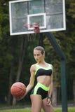 Muchacha deportiva que se coloca con una bola del baloncesto Imagenes de archivo