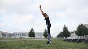 Muchacha deportiva que se resuelve en el entrenamiento de la fuerza del crossfit de la hierba en el estadio almacen de video