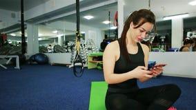 Muchacha deportiva que sonríe en la cámara que hace la imagen del selfie en el gimnasio, selfie en el gimnasio, comunicación del  almacen de metraje de vídeo