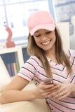 Muchacha deportiva que usa la sonrisa del teléfono móvil Fotos de archivo