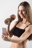 Muchacha deportiva sonriente que lleva a cabo pesa de gimnasia y tomar el selfie con smar Imagen de archivo