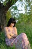 Muchacha deprimida hermosa que se sienta solamente en prado del verano Fotografía de archivo libre de regalías