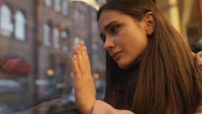 Muchacha deprimida que se sienta en autobús, saliendo del país y diciendo adiós a la ciudad natal metrajes