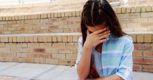 Muchacha deprimida que se sienta en las escaleras en campus metrajes