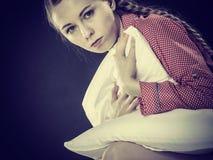 Muchacha deprimida triste en almohada conmovedora de la cama Foto de archivo libre de regalías
