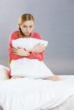 Muchacha deprimida triste en almohada conmovedora de la cama Imagen de archivo