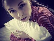 Muchacha deprimida triste en almohada conmovedora de la cama Foto de archivo