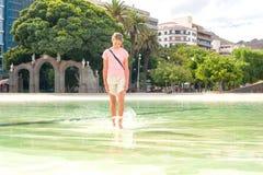 Muchacha descalza adolescente que camina en el agua de la piscina de la ciudad Imagen de archivo