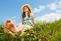 Muchacha descalza de los jóvenes que se sienta en prado Imagen de archivo