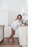 Muchacha descalza en la camisa que se coloca en la cocina Foto de archivo
