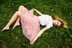 Muchacha descalza que descansa sobre la hierba Fotografía de archivo