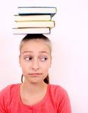 Muchacha desconcertada con los libros en su cabeza Fotografía de archivo