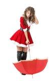 Muchacha desconcertada linda de Papá Noel con el paraguas y la cabeza del rasguño que miran abajo Imagen de archivo