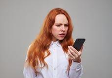 Muchacha desconcertada que mira la pantalla del teléfono Foto de archivo