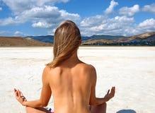Muchacha descubierta que se sienta en un lago de sal Imagenes de archivo