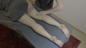 Muchacha desnuda cubierta con una toalla y la mentira en una cama que consigue un masaje de las piernas en el centro del balneari almacen de video