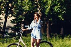 Muchacha despreocupada con una bicicleta Fotos de archivo