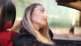 Muchacha despreocupada, de pelo largo en las gafas de sol transparentes que conducen su coche del cabriolé en la ciudad Mujer pen metrajes