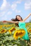 Muchacha despreocupada feliz del verano en campo del girasol Imagen de archivo