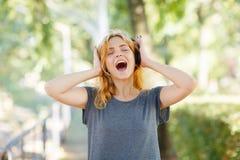 Muchacha despreocupada moderna que se divierte con los auriculares en un fondo del parque Concepto de la vida del estudiante Copi Fotografía de archivo
