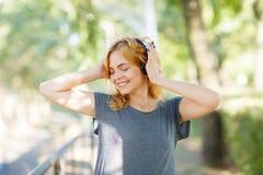 Muchacha despreocupada moderna que se divierte con los auriculares en un fondo del parque Concepto de la vida del estudiante Copi Foto de archivo libre de regalías