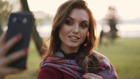 Muchacha despreocupada que sonríe y que presenta en el smartphone para los selfies en parque soleado del otoño metrajes