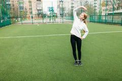 Muchacha después de entrenar, de correr o de deportes un resto en el primero plano, una botella de agua La muchacha trabaja en el fotos de archivo