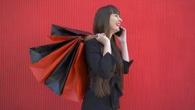 Muchacha después de que el hacer compras hable alegre en el teléfono y hable de compras acertadas con las bolsas de papel en sus  almacen de metraje de vídeo