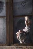 Muchacha detrás de la ventana con una taza de café o de té Fotos de archivo libres de regalías