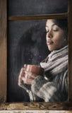 Muchacha detrás de la ventana con una taza de café o de té Foto de archivo libre de regalías