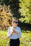 muchacha Dieciséis-año-vieja en gafas de sol y una camisa blanca que sostiene un pequeño ramo de margaritas del campo en el veran fotos de archivo libres de regalías
